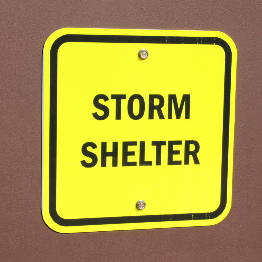 Yellow Storm shelter sign on wall