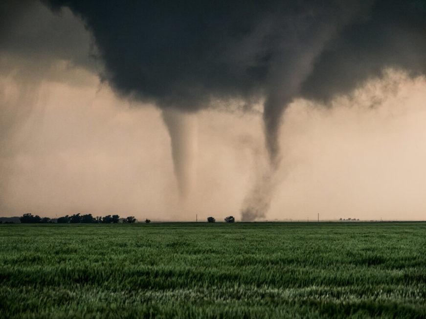 Twin tornadoes forming in field