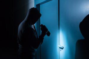 Burglar standing outside of a door